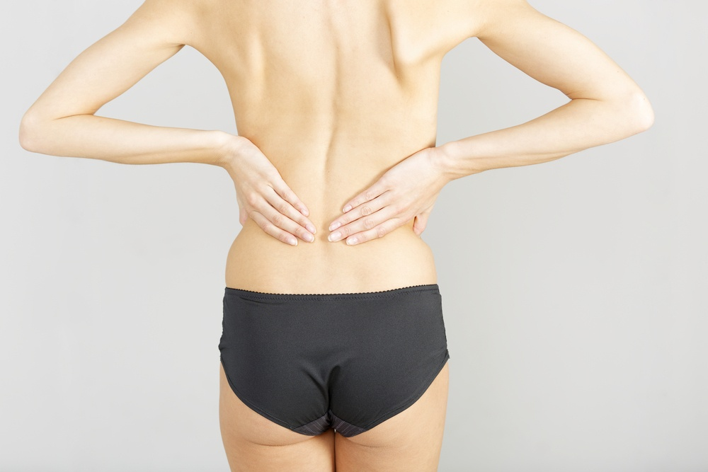 Young woman facing away massaging her lower back from an ache or pain
