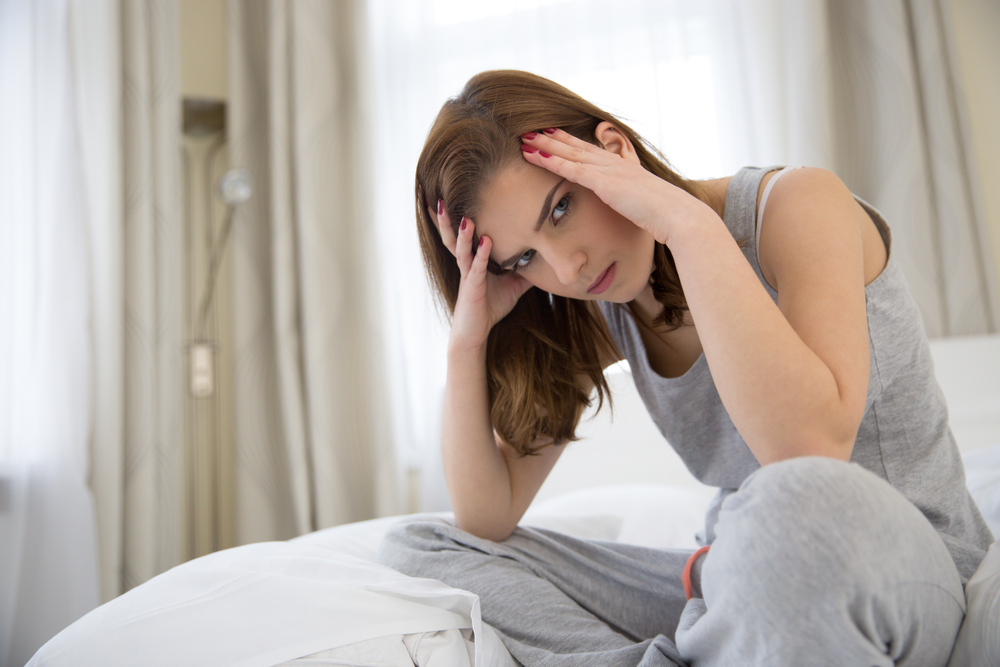 Young woman holding her head in pain suffering from a headache