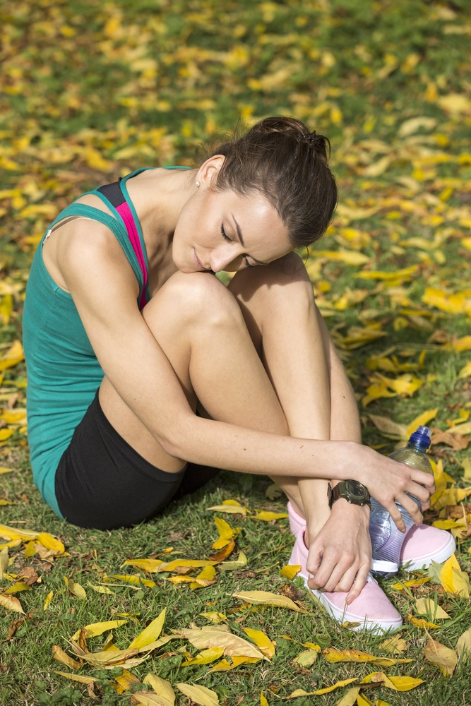Young woman resting after a long run in the forest on a beautiful sunny autumn day