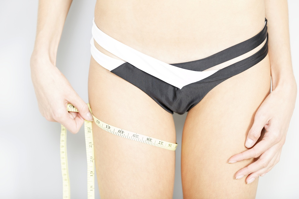 Young woman using measuring tape to measure weight loss-1