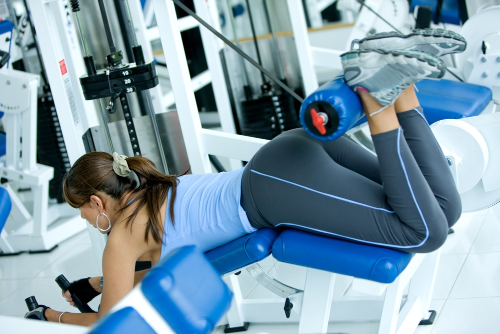 woman at the gym doing back exercises on a machine