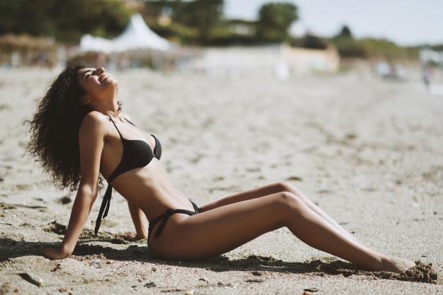 young-arabic-woman-with-beautiful-body-in-swimwear-lying-on-the-beach-sand_1139-1582